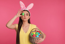 Beautiful Woman In Bunny Ears Headband Holding Basket With Easter Eggs On Color Background, Space For Text
