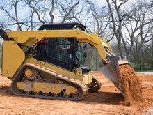 Skid Steer Loader Dumping Dirt...