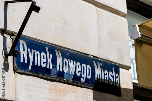 Fototapeta Warsaw, Poland New town historic road during sunny summer day morning with closeup of street sign and text for Rynek Nowego Miasta in Polish obraz