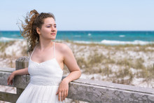 Destin, USA Miramar Beach City Town Village Day In Florida Panhandle Gulf Of Mexico Ocean Water Young Woman Girl In White Dress Leaning On Wooden Fence Railing By Sand Dunes