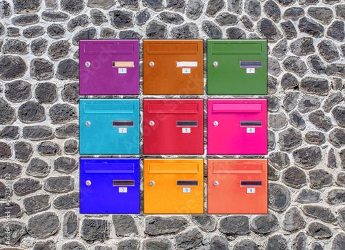 Obraz na plátně Boîtes aux lettres couleurs incrustées dans un mur de pierres