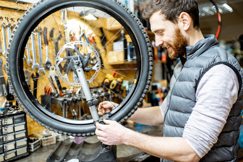 Fototapeta Man aligning bicycle wheel tensing spokes with a special key at the working place of the workshop obraz