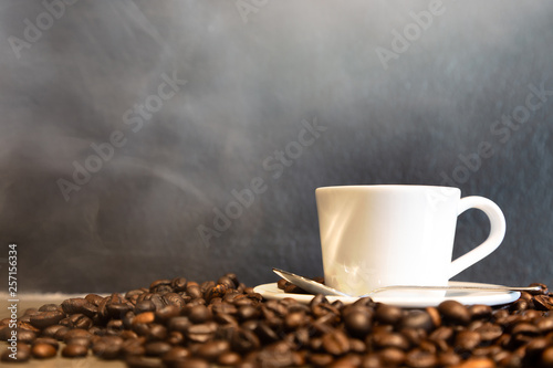 Poster Café en grains Espresso in a cup of hot coffee and coffee beans on black wall background in a cafe shop,fresh espresso with hot steam and smoke in the morning, copy space