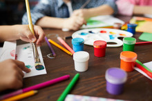 Closeup Of Children Painting Pictures, Focus On Art Supplies Paints, Pencils And Crayons, Copy Space