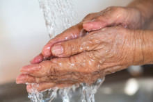 Senior Woman Washing Her Hands...