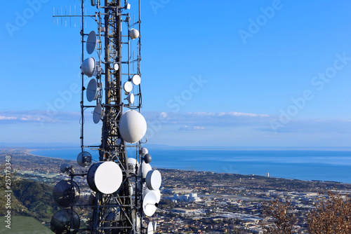 Fotografía  Telecommunications tower, antenna and satellite dish and coastline as background