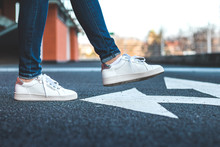 White Sneakers On Asphalt Road With Arrow Traffic Directional Sign
