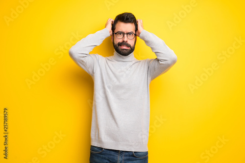 Fotografie, Obraz  Man with beard and turtleneck takes hands on head because has migraine