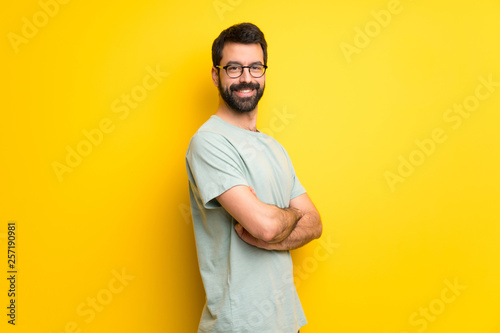 Fotografia  Man with beard and green shirt keeping the arms crossed in lateral position whil