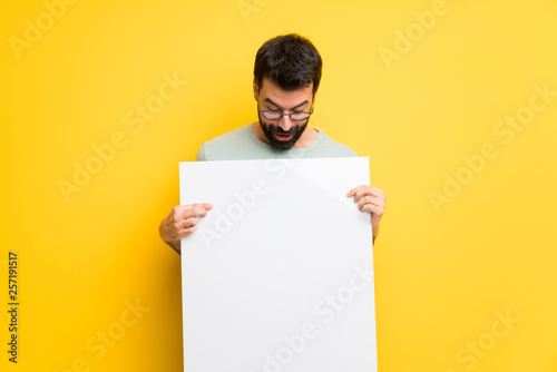 Fotografía  Man with beard and green shirt holding an empty white placard