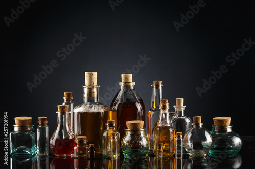 Fotografia  Glass bottles of different shapes and sizes filled with liquids of different colors on a black background