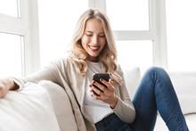 Beautiful Blonde Woman Posing Sitting Indoors At Home Using Mobile Phone.