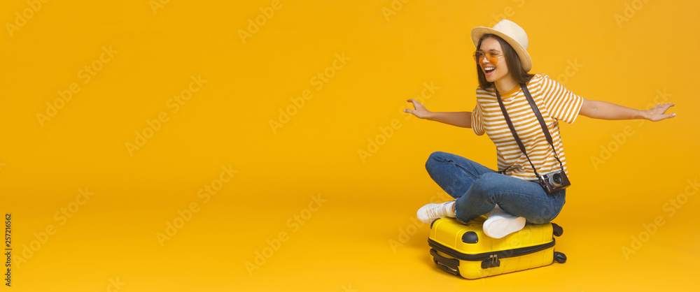 Fototapeta Horizontal banner of young tourist girl sitting on suitcase, pretending flying on a plane, isolated on yellow background with copy space. Dreams about traveling concept