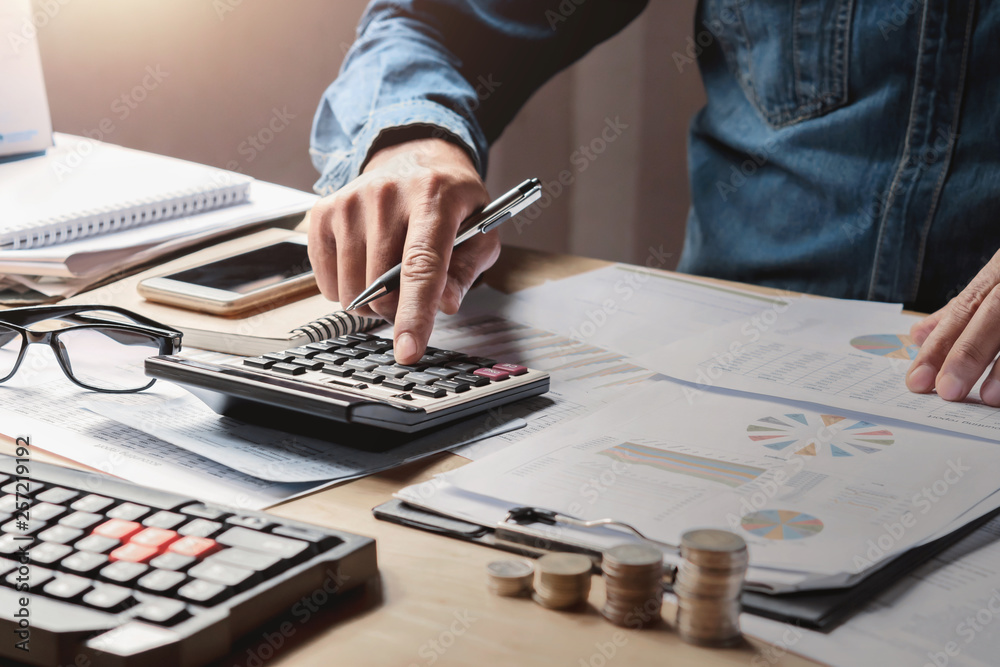 Fototapeta businessman working in office with using a calculator to calculate the numbers finance accounting concept