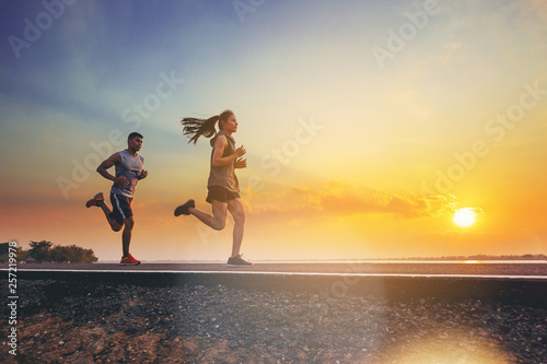 obraz dibond Young couples running sprinting on road. Fit runner fitness runner during outdoor workout with sunset background