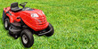 Leinwanddruck Bild - Gardening equipment advertisement template - red tractor mower on a green grass in the garden with copy space.