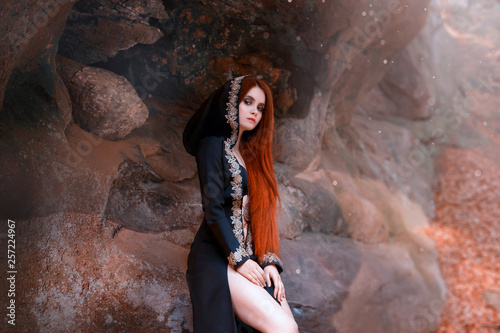 Photo mysterious young attractive lady in a long black cloak with a hood sits alone in