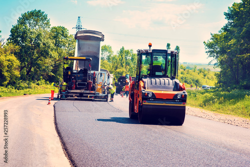 Fotografiet  industrial landscape with rollers that rolls a new asphalt in the roadway