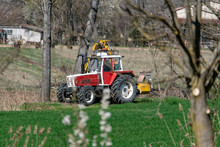 Trattore Rosso E Bianco Che Rasa Erba E Sponde Dei Campi Per Le Coltivazioni Agricole