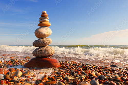 Stampa su Tela Rock zen pyramid of multi-colored pebbles in the pink rays of the setting sun against the sea