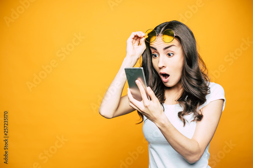 Oh, my! Gorgeous girl with a phone in her hand is surprised by something she saw on the screen is holding her glasses in front of bright yellow background Fototapet