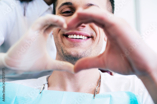 fototapeta na szkło Cheer of heart. A patient with white and healthy smile in the center of a heart made from two hands of a doctor and a patient which is telling about pleasant emotions of the appointment.