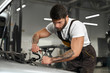 Muscular mechanic in coveralls, white t shirt repairing car.