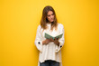 canvas print picture - Blonde woman over yellow wall holding a book and enjoying reading