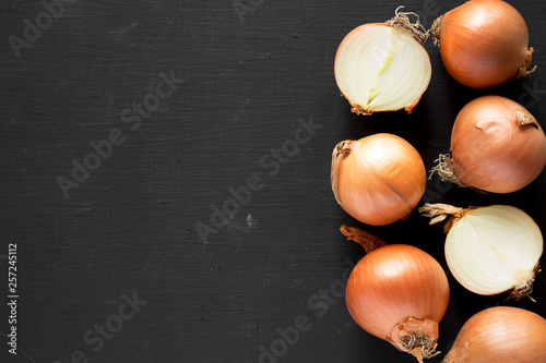 Unpeeled raw yellow onions on black surface, top view Canvas Print