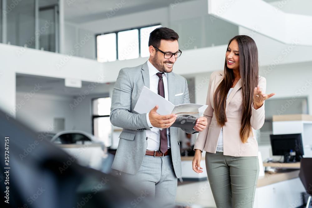 Fototapety, obrazy: Beautiful saleswoman presenting cars to a customer