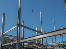 2 Ironworkers Are On A Horizontal Steel I-beam Just Put Into Place. Both Are Beginning To Put Bolts At Each End Of The Beam. 2 Working On The Steel Structure Of A Building. Blue Sky Is Behind.