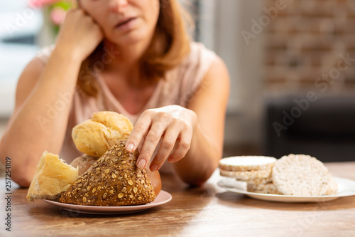 Fotografia  Woman allergic to gluten taking little bun with seeds