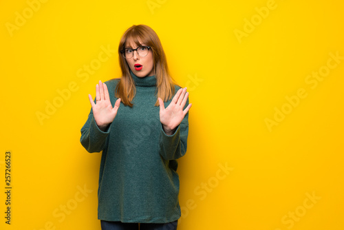 Fototapeta Woman with glasses over yellow wall making stop gesture with both hands obraz na płótnie