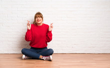 Redhead Woman Siting On The Floor With Fingers Crossing And Wishing The Best