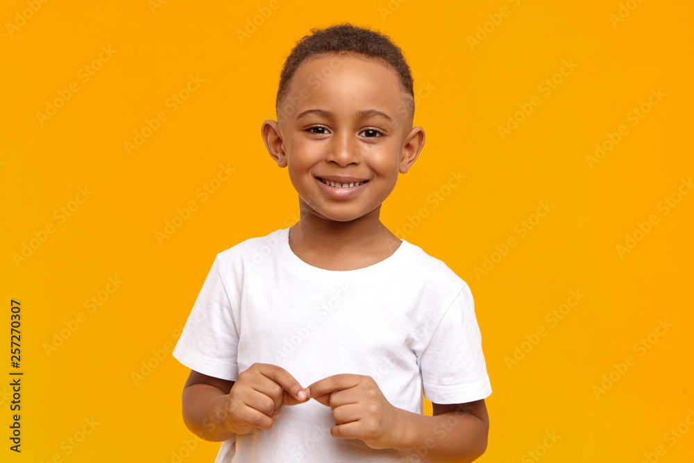 Fototapety, obrazy: People, childhood, school age and lifestyle concept. Horizontal studio image of handsome adorable African American schoolboy dressed in white t-shirt, looking at camera with broad happy smile