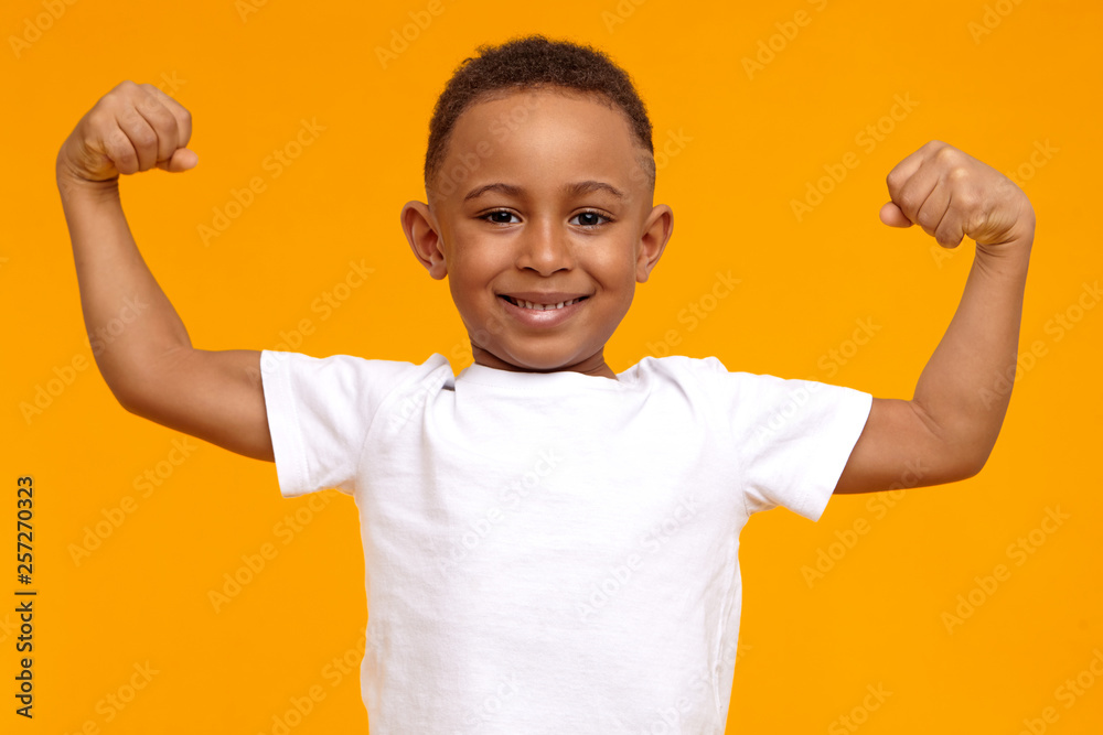 Fototapeta Handsome confident Afro American eight year old child in casual t-shirt smiling happily and raising clenched fists, tensing muscles, feeling strong and full of energy after ate healthy protein lunch
