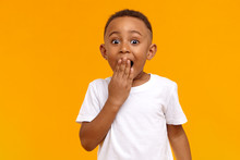 Wow. Studio Shot Of Emotional Adorable African American Little Boy Raising Eyebrows And Covering Open Mouth With Hand Being Surprised And Shocked, Showing True Astonished Reaction On Unexpected News