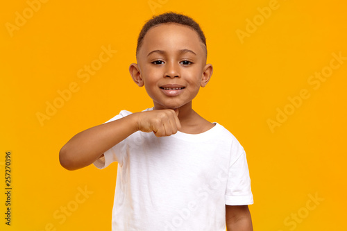 Fototapeta I will cut your head off. Picture of positive cheerful dark skinned schoolboy having fun in yellow studio, making joke, holding thumb at his neck, showing menacing warning gesture, smiling broadly obraz na płótnie