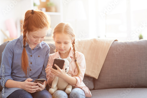 Photo Portrait of two children using gadgets at home scrolling through social network