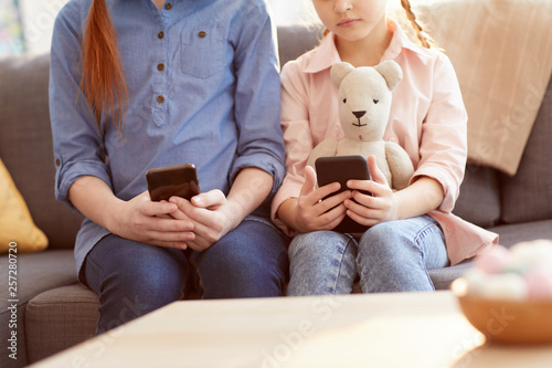 Close up of two children using smartphones at home texting and scrolling through Wallpaper Mural