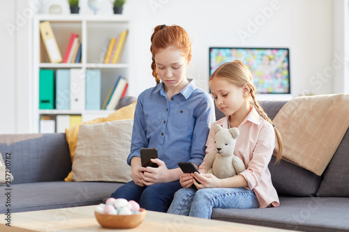 Photo  Portrait of two children using smartphones at home texting and scrolling through