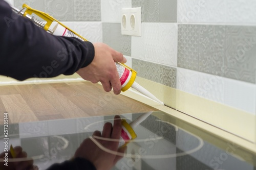 Obraz Applying silicone sealant with construction syringe. Worker fills seam between the ceramic tiles on the wall and kitchen worktop - fototapety do salonu