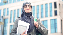 Inspired Young Female Student Wearing Hijab Smiling, Standing Outdoors On Campus