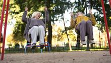 Two Elderly Women Laughing Riding Swings In Park, Elderly Friends, Retirement