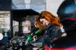 Adventurous woman fills the gasoline bike