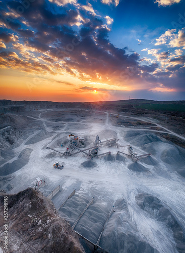 Garden Poster Panoramic view at sunset of gravel quarry, mining of yellow construction gravel, pumping gravel with help of powerful pumps, post-apocalyptic landscape.