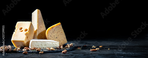 Foto Different kinds of cheese with nuts on dark background, copy space