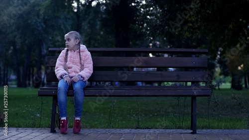 Tela Sad school girl sitting on bench in park, lost missing kid, waiting for parents