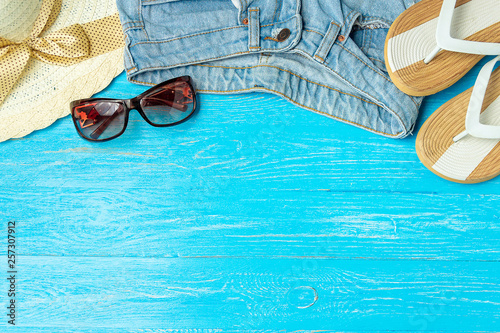 Papiers peints Retro Frame elegant female straw hat slippers jeans sunglasses on blue wooden background, copyspace for text, summer vacation.
