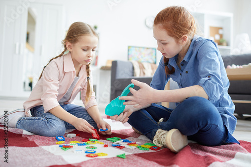 Full length portrait of two sisters playing with puzzles sitting on floor, copy Canvas Print